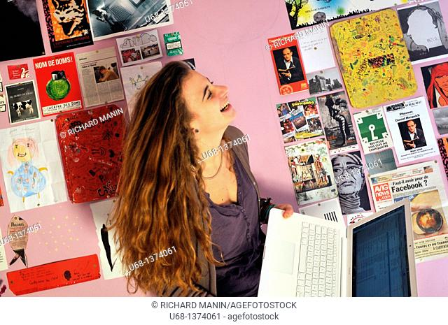 Teen girl in her bedroom with laptop computer, laughing
