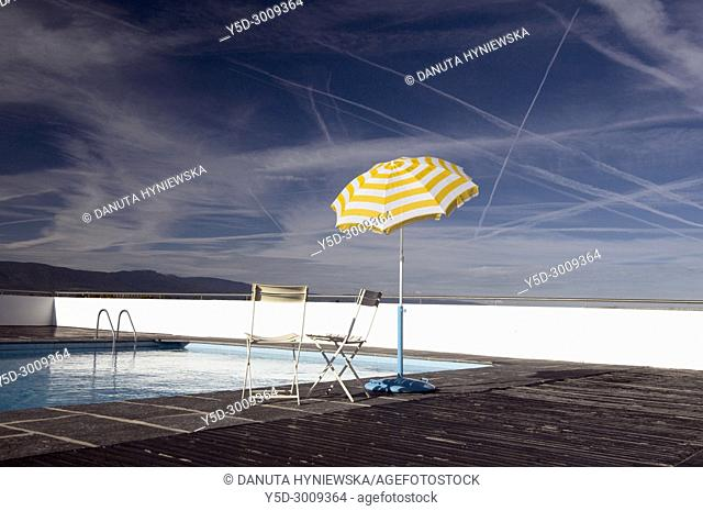 empty swimming pool in Geneve, Switzerland, umbrella and sky,