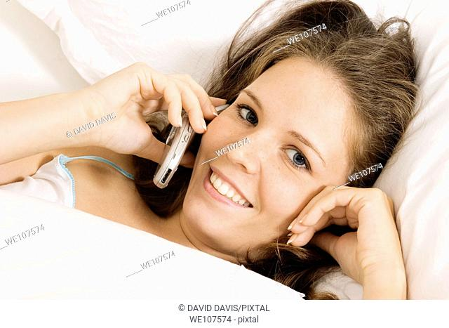 Caucasian woman in early 20's laying in bed talking on cell phone