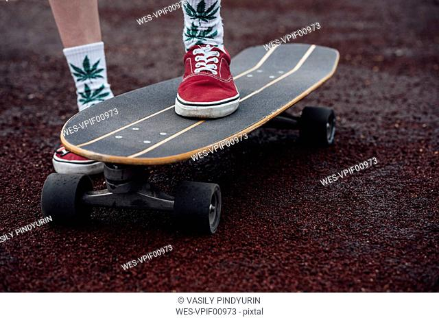Woman's legs in socks and sneakers standing on carver skateboard