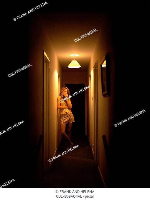 Portrait of teenage girl alone in dark corridor