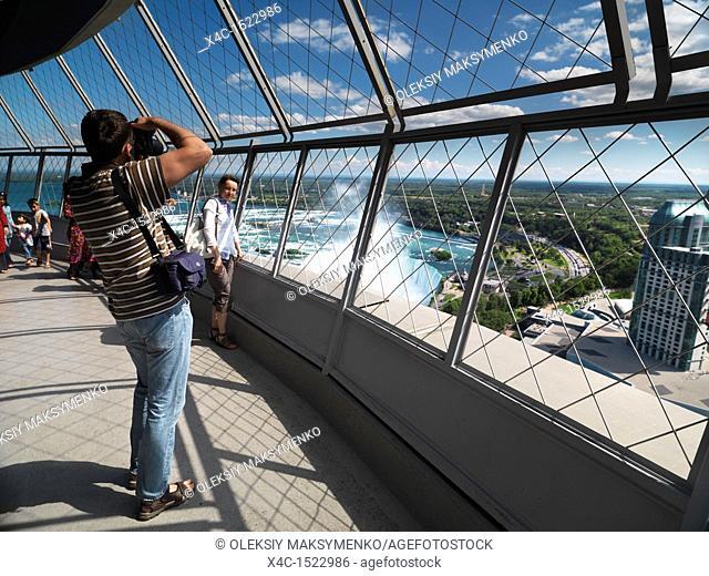 Young tourist couple photographying at Skylon tower, Niagara Falls, Ontario, Canada