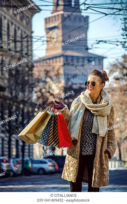 Rediscovering things everybody love in Milan. smiling trendy tourist woman with shopping bags in Milan, Italy looking into the distance