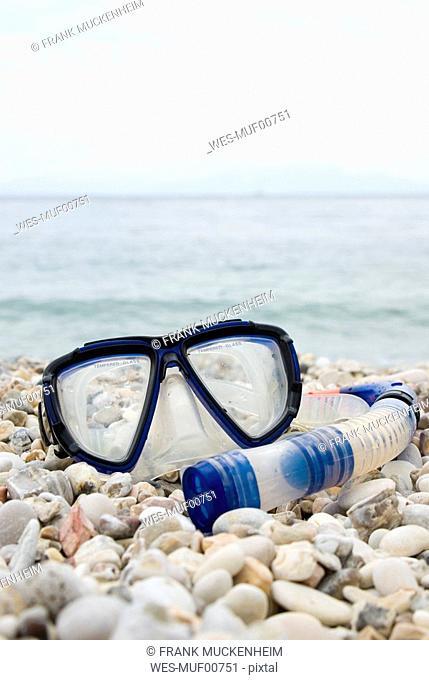 Snorkeling mask and snorkel on shingle beach