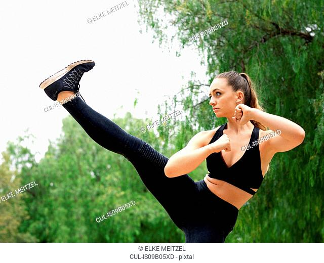 Young female kickboxer practicing kickboxing in park