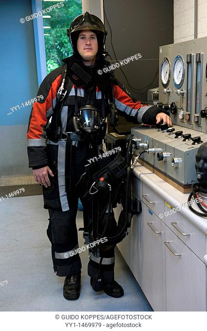 Firefighter in fireproof turnout gear on his regular job in the barracks