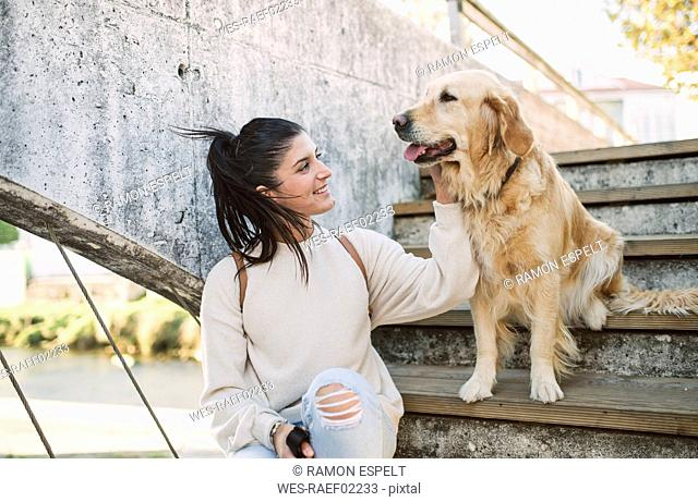 Smiling young woman stroking her Golden retriever dog on stairs outdoors