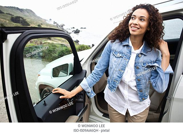 Young woman getting out of car at coast