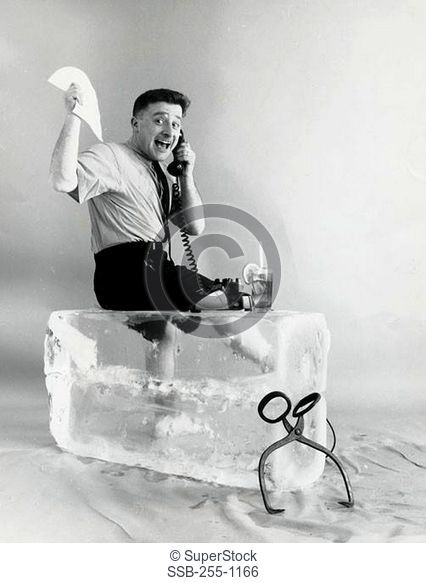 Side profile of a businessman sitting on ice using a telephone