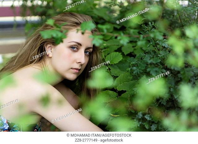 Serious young woman sitting outdoors by the trees