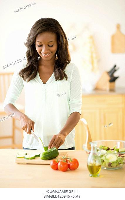 Black woman chopping vegetables in kitchen