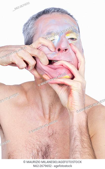 Portrait of a crazy clown, he smeared makeup on the face with his hands vigorously
