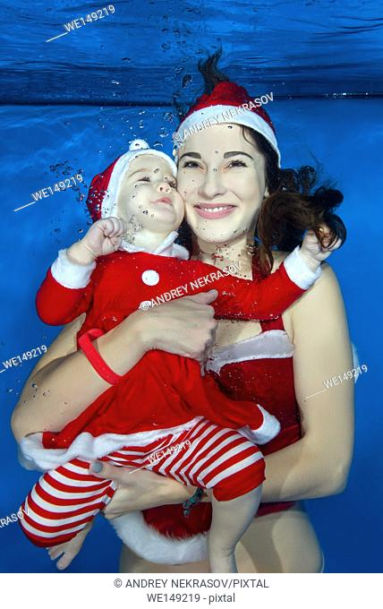 Mama and little girl dressed as Santa floats under water in the pool