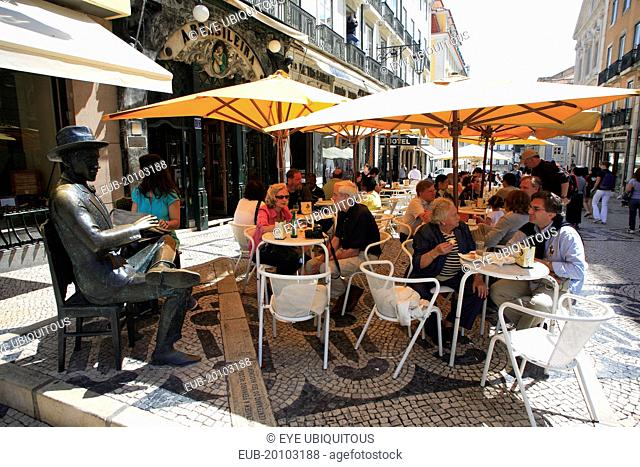 Cafe a Brasileira with people sat at outside tables beneath sunshades next to the statue of poet Fernando Pessoa