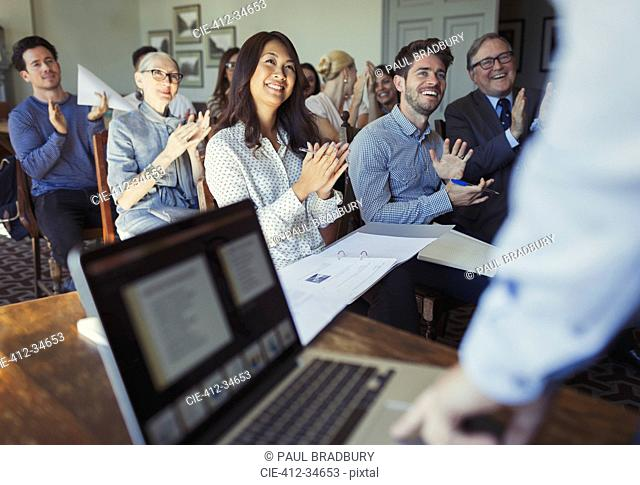 Smiling business people clapping for businessman leading conference presentation at laptop