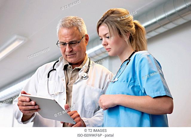 Doctors looking at digital tablet