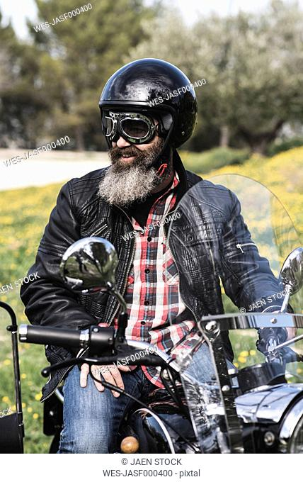 Portrait of biker wearing helmet and goggles sitting on his sidecar motorcycle