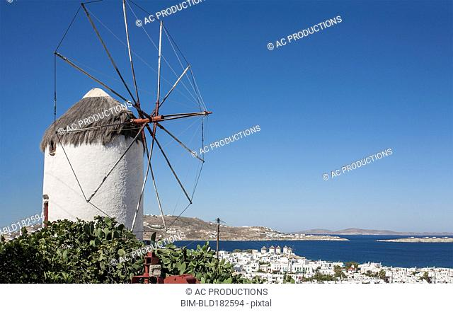 Traditional windmill and Mykonos cityscape, Cyclades, Greece