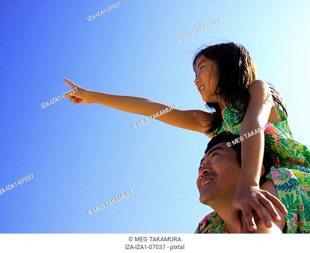Mid adult man carrying his daughter on his shoulder and smiling