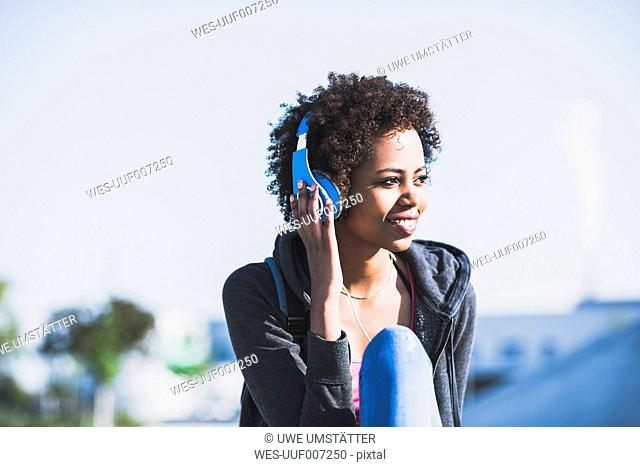 Smiling young woman wearing headphones outdoors