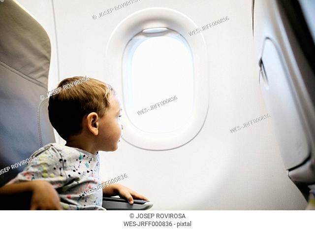Little boy looking out of window while flying on an airplane