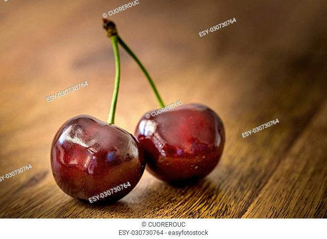 two cherries on wooden table