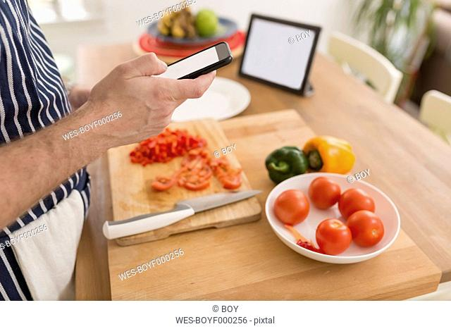 Man using smartphone while preparing food in the kitchen, close-up