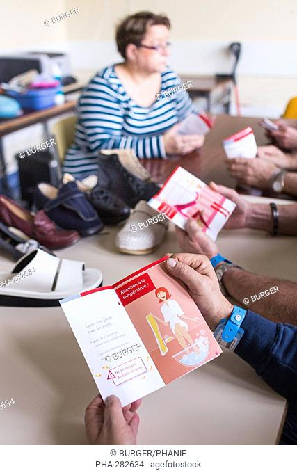 Diabetic patient participating in foot hygiene therapeutic education worksop with caregiver, Limoges hospital, France