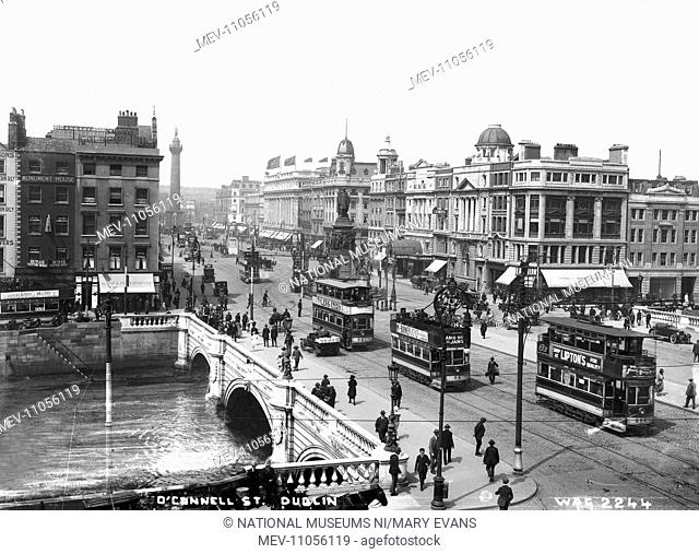 O'Connell St. Dublin - a busy street scene looking down on the bridge with trams, people and motor vehicles and shop fronts
