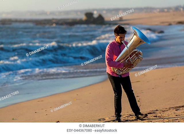 Musician play Tuba on the ocean coast