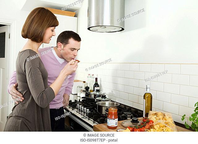 Man tasting pasta sauce that wife is making