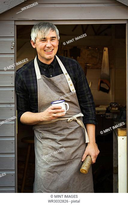 A craftsman wearing a work apron standing in doorway of a workshop, holding mug and small log of wood, smiling. Tea break