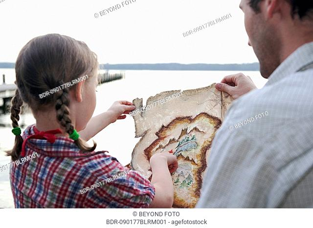 young girl and father looking at treasure map