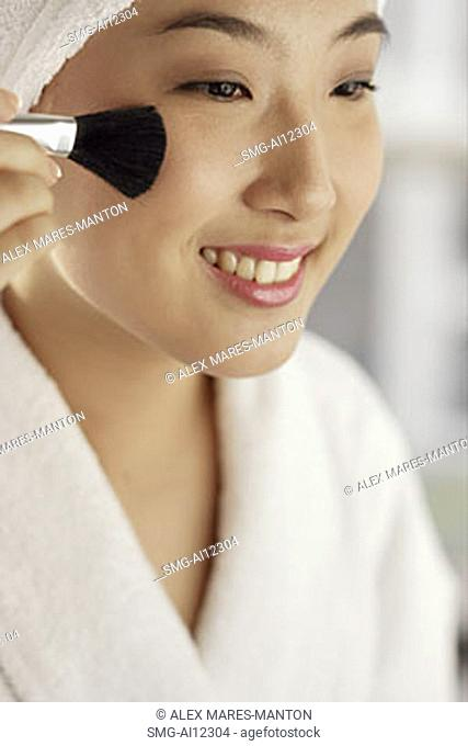 Young woman with make-up brush, smiling
