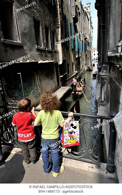 Children watching the gondolas in a canal, Venice, Veneto, Italy