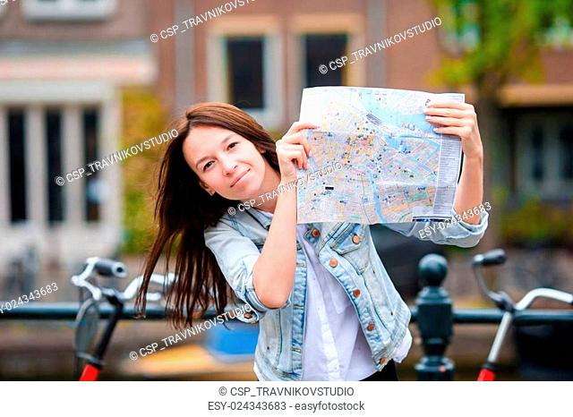 Happy young woman with a city map in european city