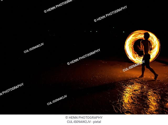 Young man displaying a fire poi show on the beach, Koh Samet, Thailand