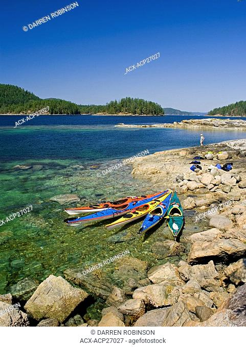 Woman enjoys breathtaking scenery from the shores of Desolation Sound during a sea kayak excursion near Powell River on the Sunshine Coast of British Columbia