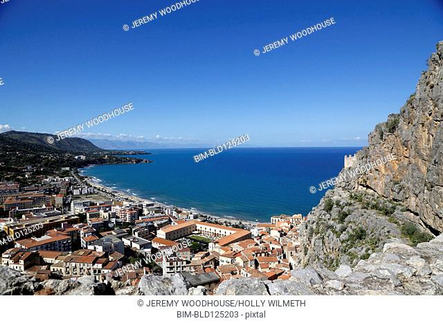 Cefalu and ocean viewed from rocky hillside, Cefalu, Sicily, Italy