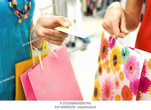 Close-up of womans hand holding credit card and bags with another female near by during shopping in the mall