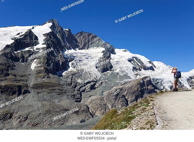 Austria, Carinthia, female hiker with binoculars watching Grossglockner peak, High Tauern National Park