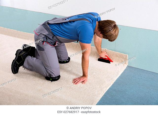 Young Male Craftsman Fitting Carpet On Floor