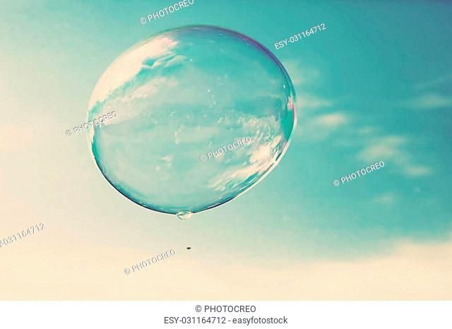 One clean soap bubble flying in the air, blue sky. Sun reflection, vintage style