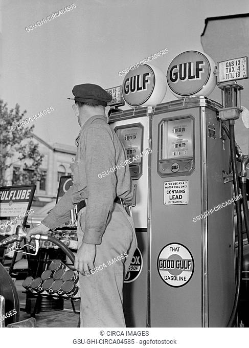 Gas Station Attendant Pumping Gas while Keeping an eye on Gauge during Gasoline Rationing, USA, Office of War Information, 1940's