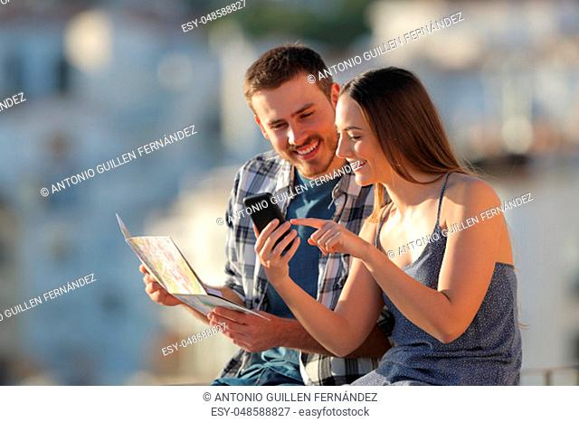 Happy couple of tourists comparing smartphone content and paper map in a town on vacation