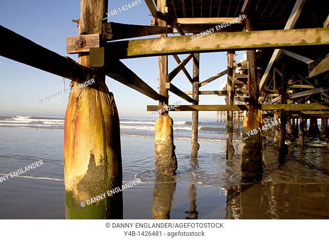 A reflection forms in the seawater washing in underneath a pier, Chrystal Pier Hotel, Pacific Beach, San Diego, California