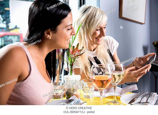 Friends using smartphone during lunch in restaurant