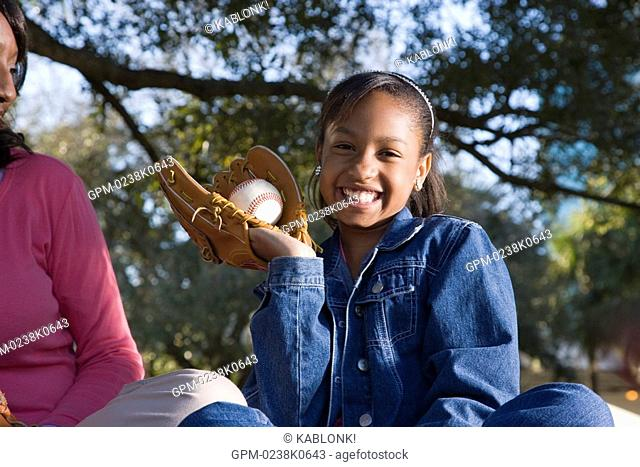 Portrait of African American girl holding a softball in softball glove, looking at camera