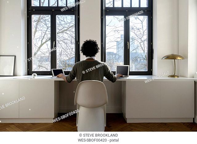 Man working in front of panorama window at home with laptop and tablet