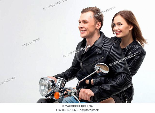 Portrait of young loving couple dating and traveling by scooter. The man is driving and smiling. The woman is sitting and embracing him with happiness